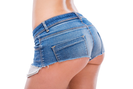 nude female buttocks: Perfect buttocks. Close-up of perfect female buttocks in jeans shorts being isolated on white background Stock Photo