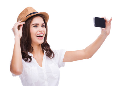 making up: I love selfie! Cheerful young woman in funky hat making selfie with her smart phone and smiling while standing against white background