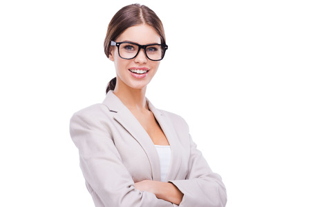 charming businesswoman: Charming businesswoman. Confident young businesswoman keeping arms crossed and smiling while standing against white background