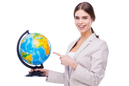 Supporting your business all around the world. Beautiful young women holding globe and pointing on it while standing against white background photo