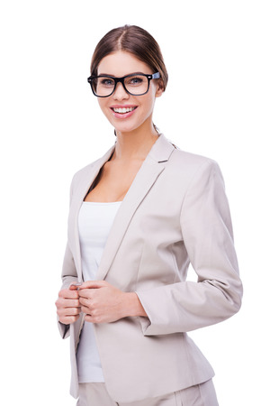 buttoning: Beautiful and smart. Confident young businesswoman adjusting her jacket and smiling while standing against white background