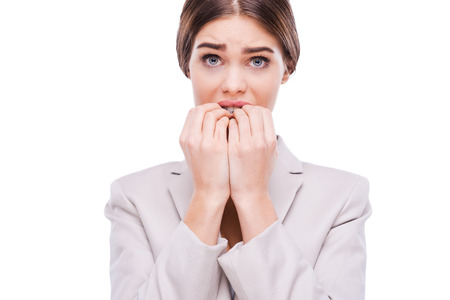 biting: A little bit nervous about this business. Nervous young businesswoman biting her nails while standing against white background Stock Photo
