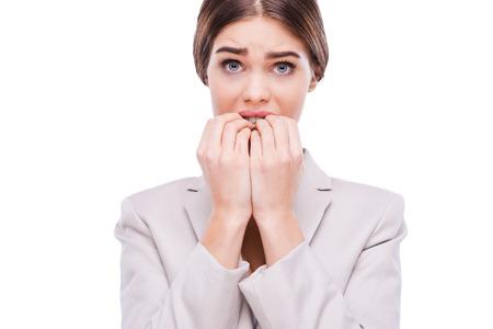 nerveux: Un peu nerveux au sujet de cette affaire. Jeune femme d'affaires nerveux se ronger les ongles tout en se tenant sur le fond blanc Banque d'images