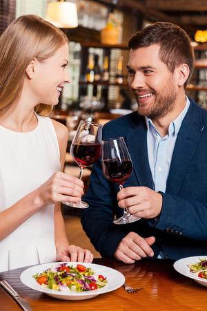 Saludos a nosotros! Hermosa joven pareja amorosa brindando con vino tinto y sonriendo mientras está sentado en el restaurante junto Foto de archivo - 36092109