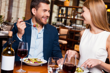 一緒に食事を楽しんでください。レストランでディナーを楽しんでいる美しい若い夫婦