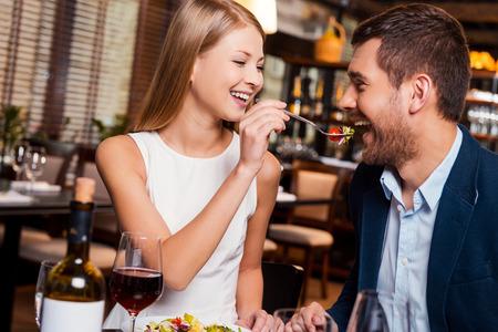 hombre comiendo: Trate de mi comida! Hermosa pareja de jóvenes amantes de cenar en el restaurante mientras que la mujer introduce a su novio con ensalada