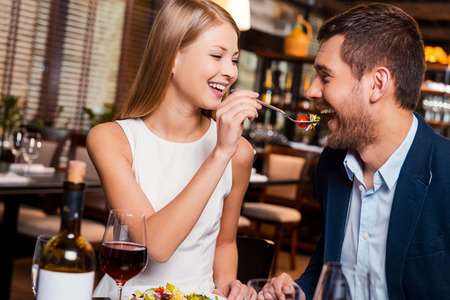 Try my meal! Beautiful young loving couple enjoying dinner at the restaurant while woman feeding her boyfriend with salad