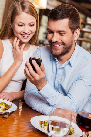just in time: Just look at this! Beautiful young loving couple enjoying time in restaurant together while man showing something at his mobile phone and smiling