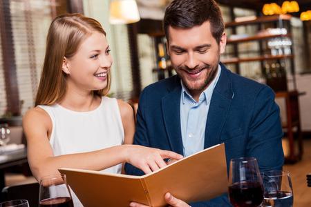 jovenes enamorados: Pruebe esta comida! Hermosa joven pareja amorosa examinar menú y sonriendo mientras está sentado en el restaurante junto Foto de archivo