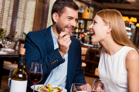 Try this! Beautiful young loving couple enjoying dinner at the restaurant while man feeding his girlfriend with salad Stock Photo
