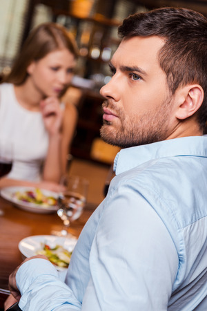 relationship difficulties: Relationship difficulties. Frustrated young man looking away while sitting together with his girlfriend in restaurant