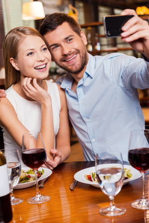 Capturing romantic moments. Beautiful young loving couple making selfie and smiling while sitting at the restaurant together photo