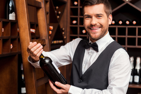 Confident sommelier. Confident male sommelier holding wine bottle and smiling while standing near the wine shelf photo