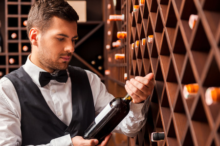 Choosing the right wine. Confident male sommelier examining wine bottle while standing near the wine shelf