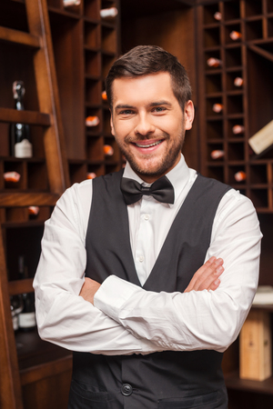 sommelier: Confident sommelier. Confident male sommelier keeping arms crossed and smiling while standing near the wine shelf Stock Photo