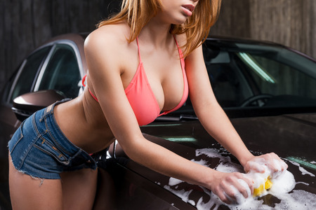 wet breast: Washing your car. Close-up of attractive young woman with beautiful cleavage washing car with sponge Stock Photo