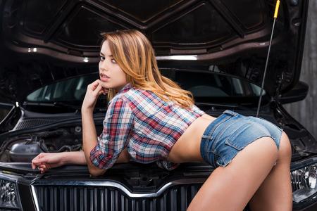 sexo: Lo s� todo sobre los coches. Mujer joven atractiva con las nalgas perfectas apoy�ndose en el coche con el cap� abierto en taller de reparaciones auto Foto de archivo
