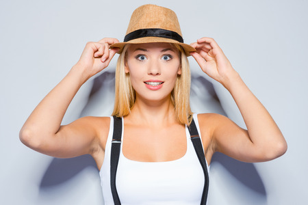 Funky beauty. Beautiful young blond hair women making a face and adjusting her hat while standing against grey background photo