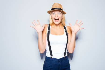 Funky emotions. Beautiful young blond hair women making a face while standing against grey background photo