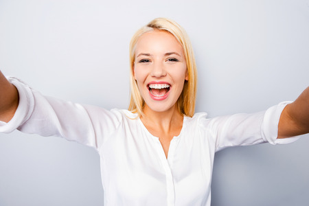 self confident: Happy moments must be saved. Cheerful young blond hair woman holding camera and making photo of herself while standing against grey background Stock Photo