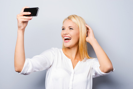 blond hair: Expert in photography. Cheerful young blond hair woman holding mobile phone and making photo of herself while standing against grey background Stock Photo