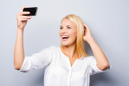cabello rubio: Experto en la fotograf�a. Mujer joven de pelo rubio alegre celebraci�n de tel�fono m�vil y hacer la foto de s� misma mientras est� de pie contra el fondo gris