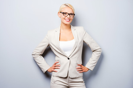 Smart and beautiful. Confident young businesswoman holding hands on hips and looking at camera while standing against grey background