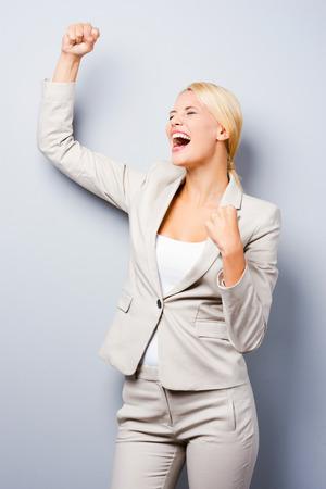 puños cerrados: ¡Qué día de suerte! La joven empresaria manteniendo Brazos felices planteadas mientras está de pie contra el fondo gris