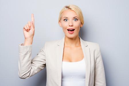 cara sorprendida: Sólo inspirado. Empresaria joven emocionada apuntando hacia arriba mientras está de pie contra el fondo gris Foto de archivo