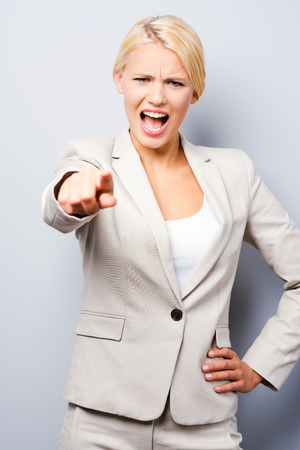 get out: Get out! Beautiful young businesswoman pointing you while standing against grey background