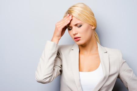 疲れを感じる。落ち込んで若い実業家触れる彼女の頬骨と目を維持する灰色の背景に対して立っている間閉鎖 写真素材 - 36293406