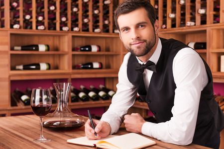 와인에 관한 모든 것을 알고 있습니다. 자신의 노트 패드에 무언가를 쓰고 배경에서 와인 선반으로 나무 테이블에 기대어 동안 카메라를 찾고 자신감