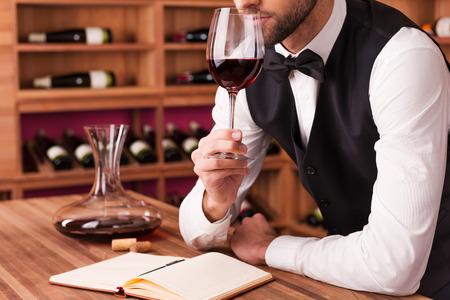 소믈리에는 와인을 검토. 그 냄새와 배경에 와인 선반과 나무 테이블에 기대어 동안 와인을 검사 확신 남성 소믈리에의 자른 이미지