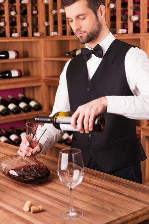 sommelier: Pouring wine to decanter. Confident male sommelier pouring wine to decanter while standing near the wine shelf