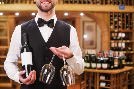 winetasting: Confident waiter. Handsome young man in waistcoat and bow tie holding bottle and glasses while standing in liquor store