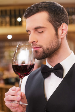 closed society: Enjoying the best wine. Confident young man in waistcoat and bow tie keeping eyes closed while holding wine glass with red wine and smelling it Stock Photo