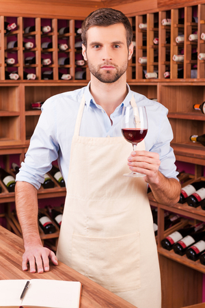 wine testing: Confident winery owner. Confident young man in apron holding glass with red wine while standing in wine cellar