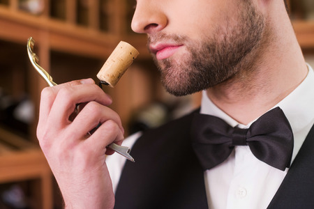 using senses: Enjoying the best wine. Close-up of confident young man in waistcoat and bow tie smelling wine cork Stock Photo