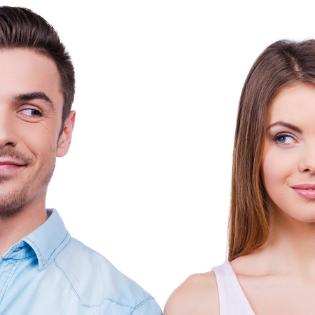 They are plotting something. Beautiful young loving couple smiling and looking at each other while standing against white background Stock Photo