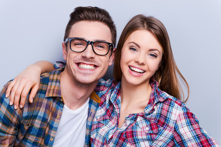 Bright smile for whole life! Beautiful young loving couple smiling at camera while standing against grey background Foto de archivo