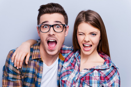making fun: Playful couple. Beautiful young loving couple making faces at camera while standing against grey background