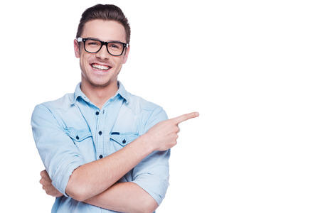 Cheerful young man pointing copy space. Handsome young man in shirt looking at camera and pointing away while standing against white background