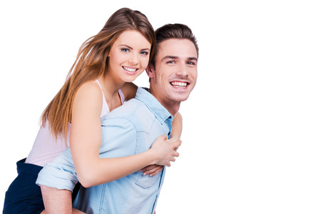 Happy couple. Happy young man carrying his beautiful girlfriend on shoulders and smiling while standing against white background