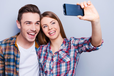 relationship love: Capturing happy moments together.  Happy young loving couple making selfie and smiling while standing against grey background