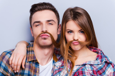 dating: Funny moustache. Beautiful young loving couple making fake moustache from hair while standing against grey background