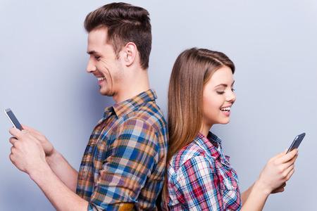 Mensagens românticas. Jovem casal amoroso bonita que prende telefones móveis e de costas para o contra um fundo cinza