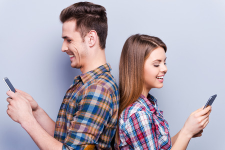 love and friendship: Romantic messages.  Beautiful young loving couple holding mobile phones and standing back to back against grey background Stock Photo