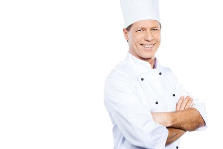 요리는 나의 열정입니다. 백인 제복을 입은 자신감이 성숙한 요리사가 넘어서 서서 웃는 동안 흰색 배경