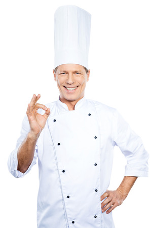 chefs whites: Confident chef. Confident mature chef in white uniform gesturing OK sign and smiling while standing against white background
