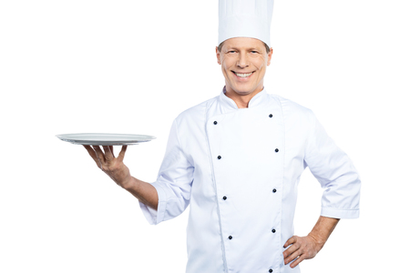 chefs whites: Copy space at his plate. Confident mature chef in white uniform holding empty plate and smiling while standing against white background